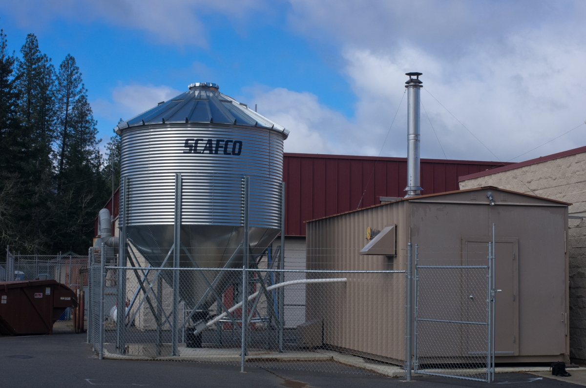 Figure 2: A biomass hopper (left) feeding into a biomass boiler room. Image courtesy of the Oregon Department of Forestry.
